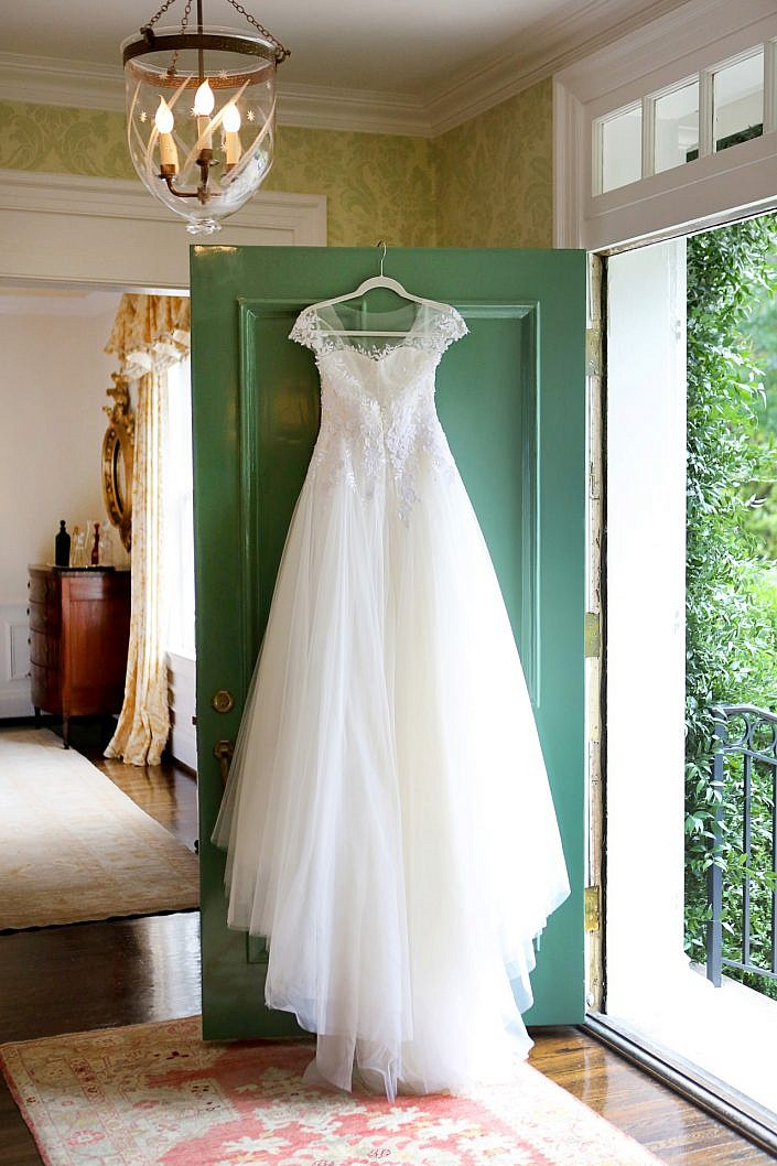 Mira Zwillinger couture wedding gown hanging on a green door