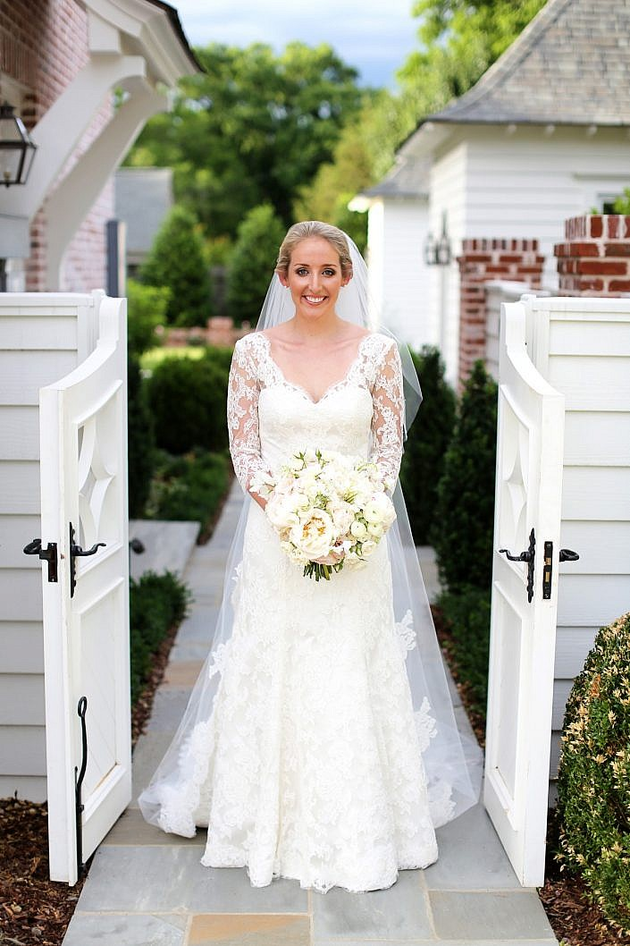smiling bride standing in garden gate