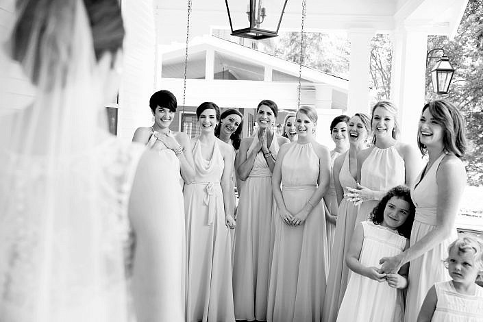 bridesmaids smiling first look with bride