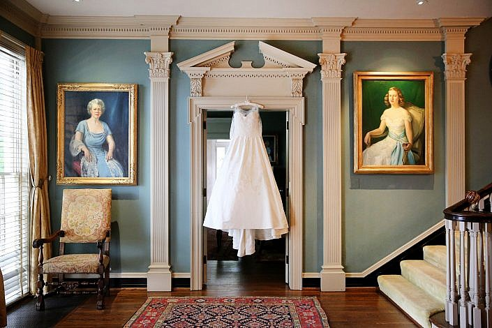 wedding gown hangs among family portraits