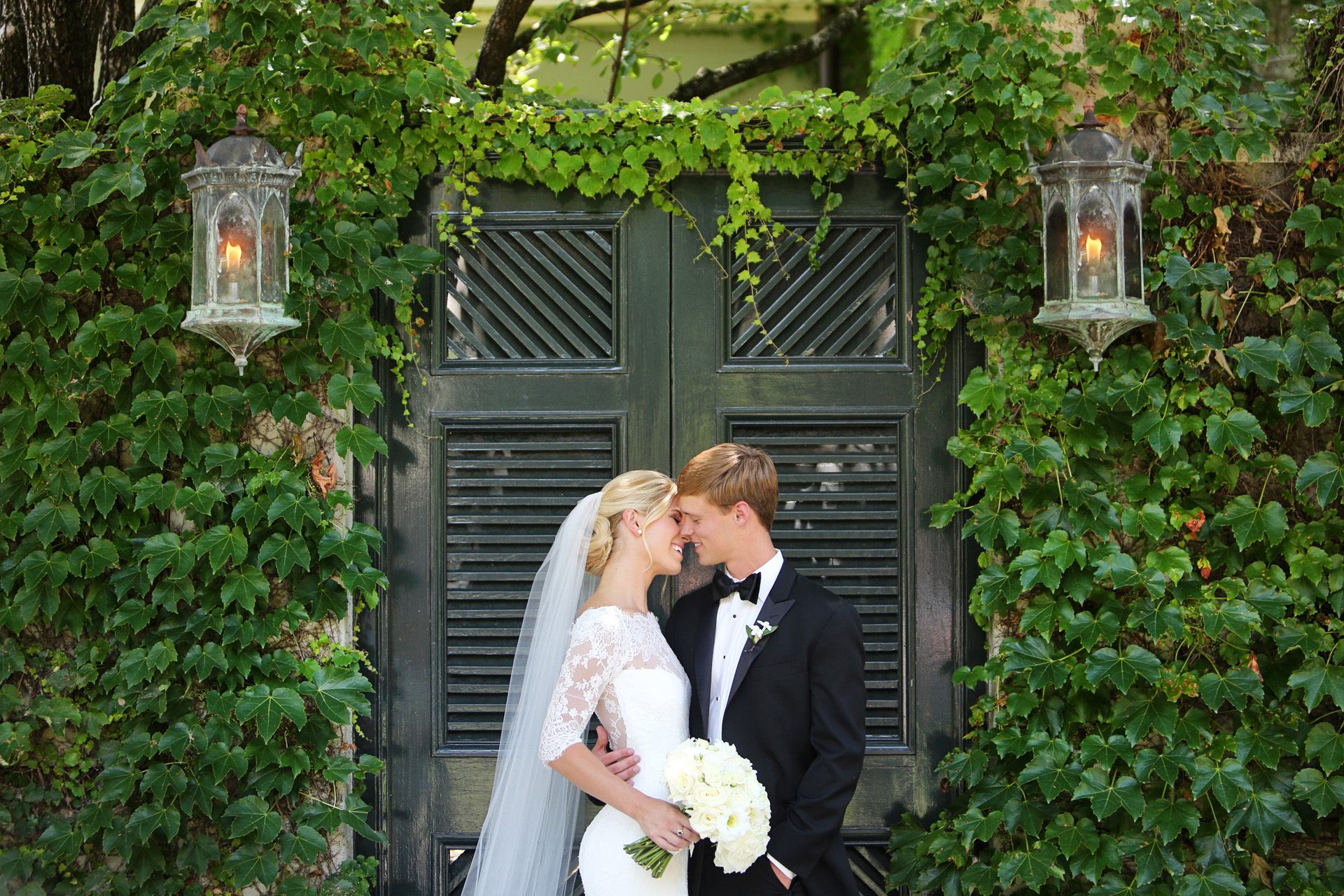 bride and groom kiss at garden gate covered with ivy